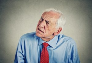 Closeup portrait headshot senior man hard of hearing asking someone to speak up can't hear isolated gray wall background.